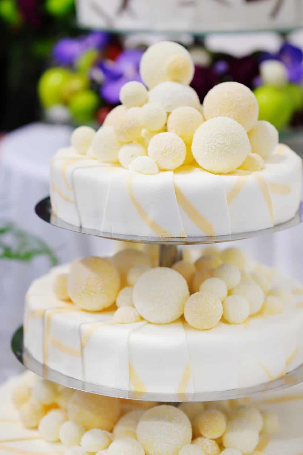 White and yellow wedding cake with delicate yellow sugar balls