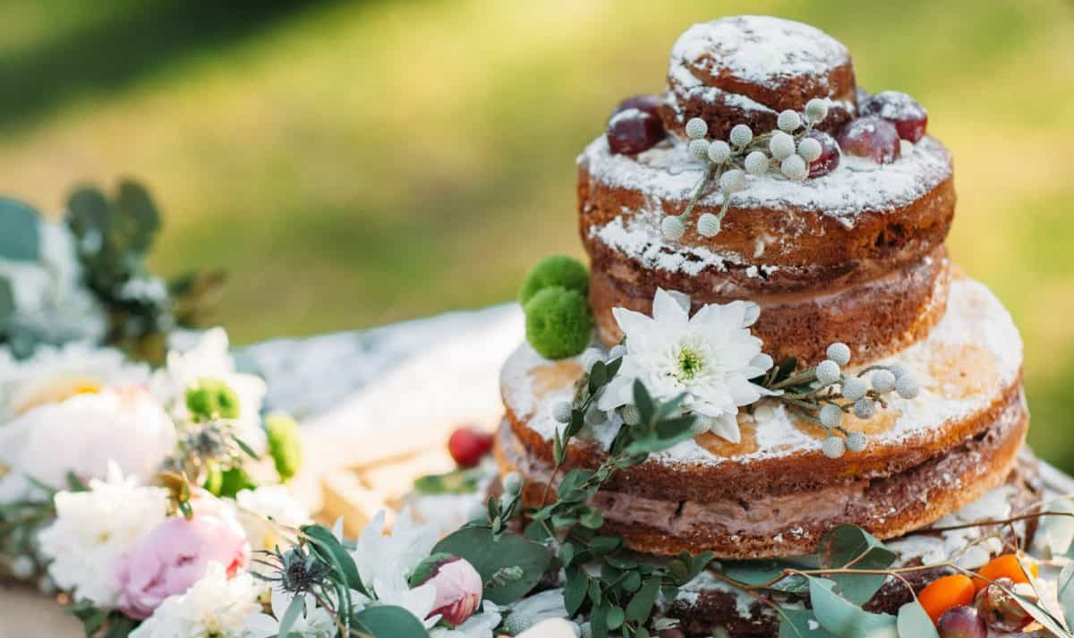 Chocolate cake on table with flowers, free space. Delicious wedding biscuit, decorated with chestnuts. Dessert, pastry, autumn , rustic , floristics concept