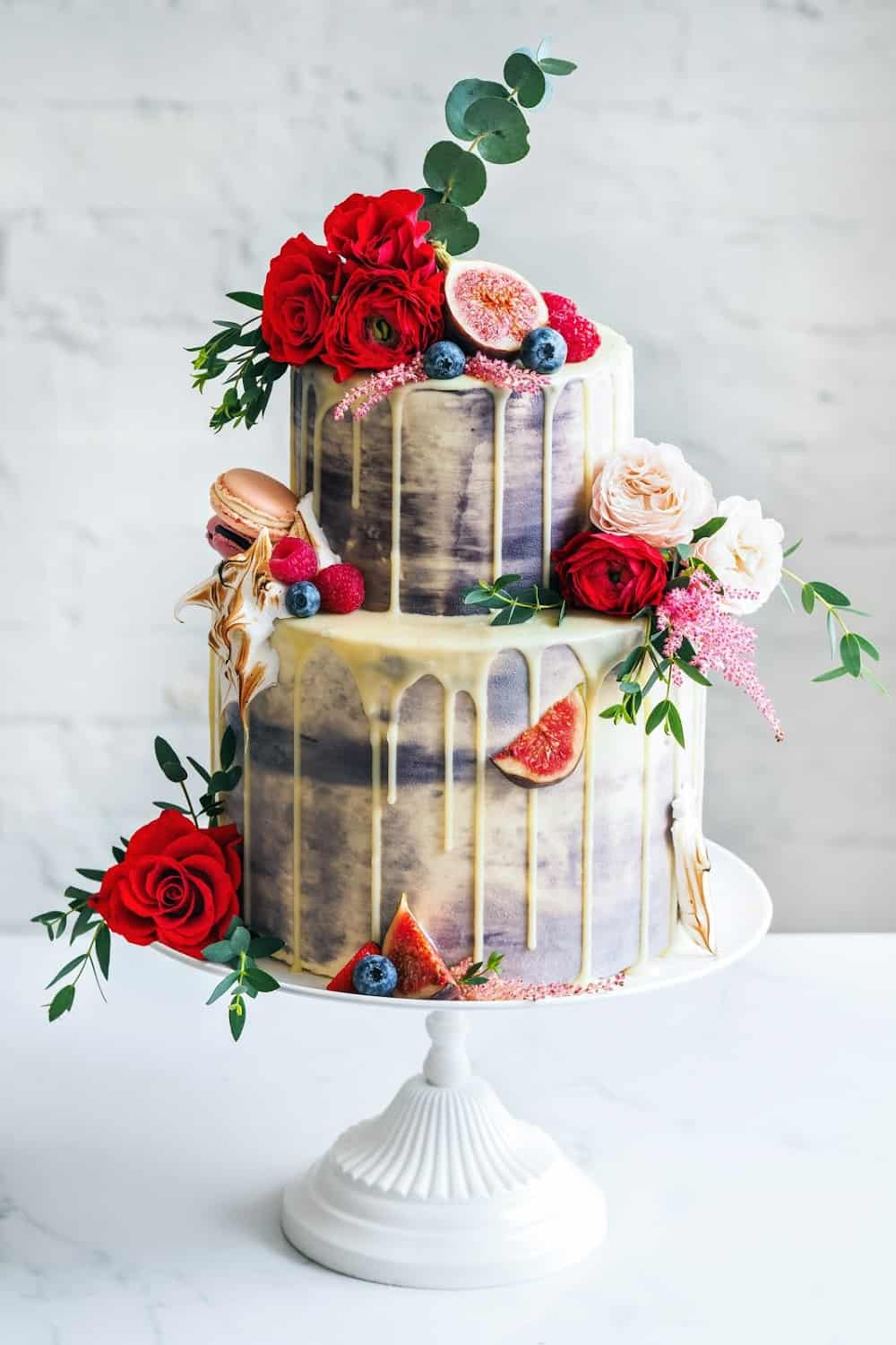 Wedding cake with flowers, figs, macarons and blueberries