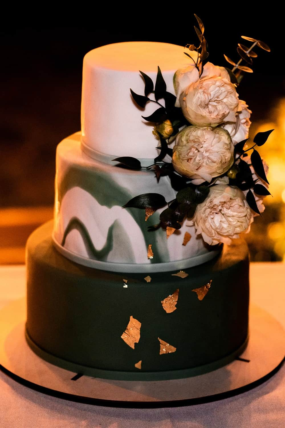 Black, white and gold wedding cake with vintage rose decorations.