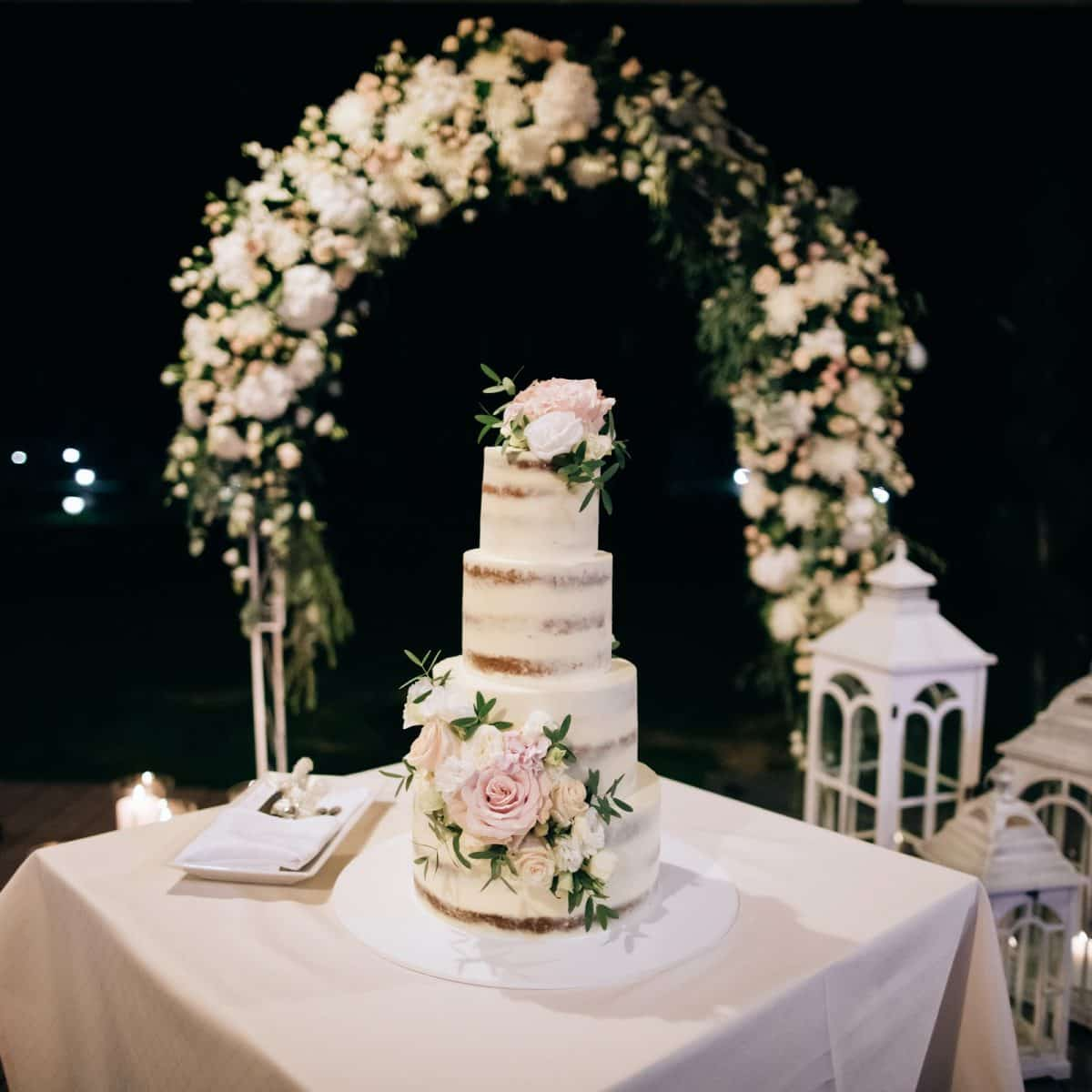 beautiful wedding cake with candles and flowers outdoors