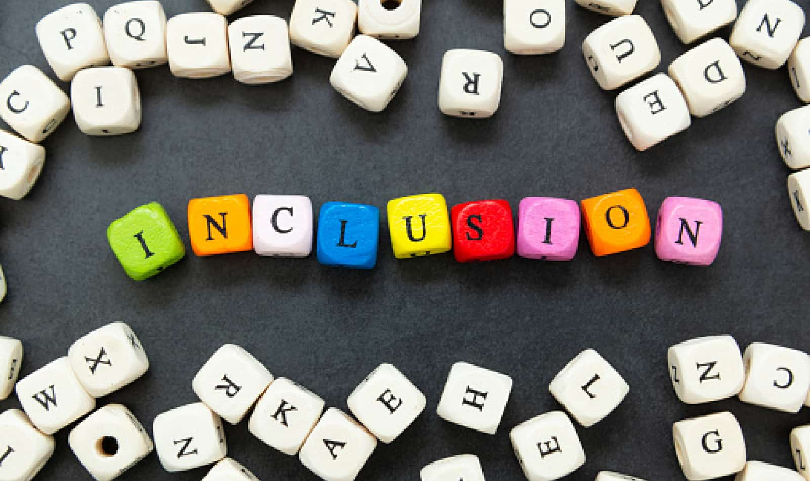 Inclusion text of multi colored cubes on dark background. Inclusive social concept. Lettering