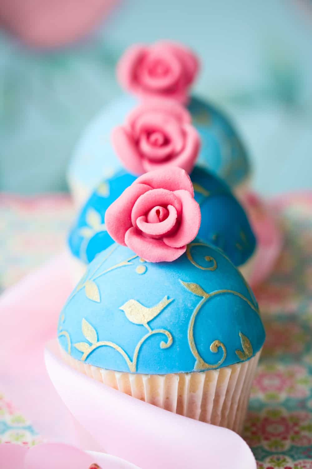 Cupcakes decorated with turquoise fondant and pink sugar roses