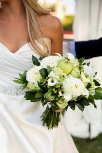 A lovely wedding bouquet made of green leaves, green fruits and white flowers