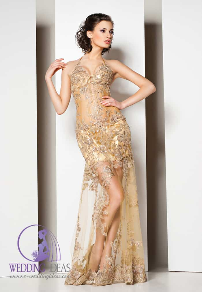 101. Gold see trough wedding dress with halter strap necklace, whole in crystals. Pinned up brown hair and strong make up. You can also see black high heels hiding in the skirt.