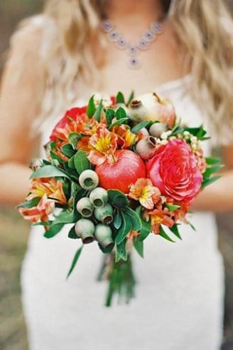 A lovely wedding bouquet comprised of green and red fruits, round red flowers and green leaves