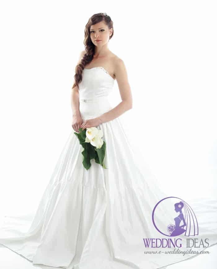 Wedding dress has straight necklace with few crystals on the top of bust. Delicate belt in the waist and very long pleated skirt with train.
