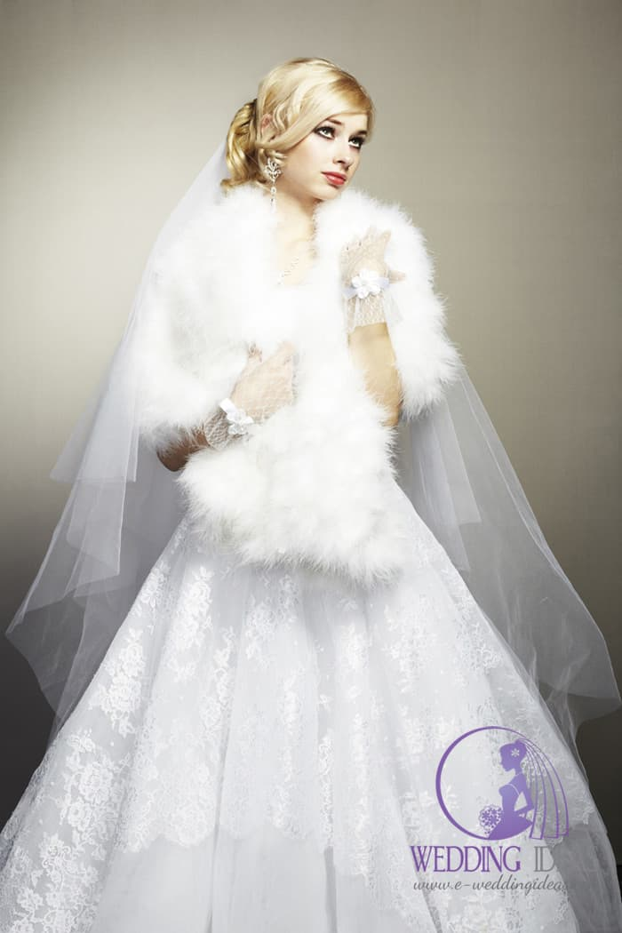 105. Bodice hide under white faux fur. Flared lace and tulle skirt. Very long veil pinned in blonde hair. Lace short gloves with big flower in the middle. Strong make up and long crystal earring.