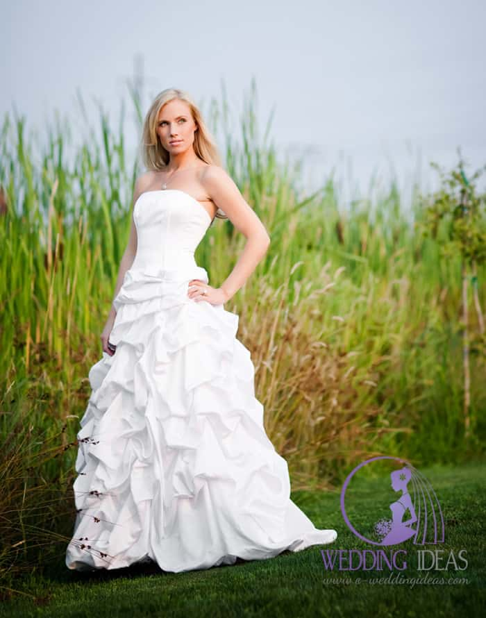 11. Satin wedding dress with straight necklace and gathered skirt. Long blonde hair and silver necklace, light make up looking good in all styling.
