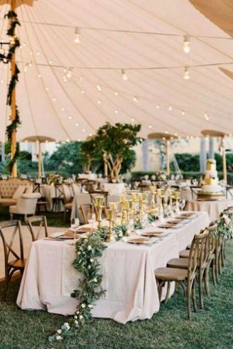 A romantic white wedding tent with brown seats, white table clothes, white lights and pink flowers