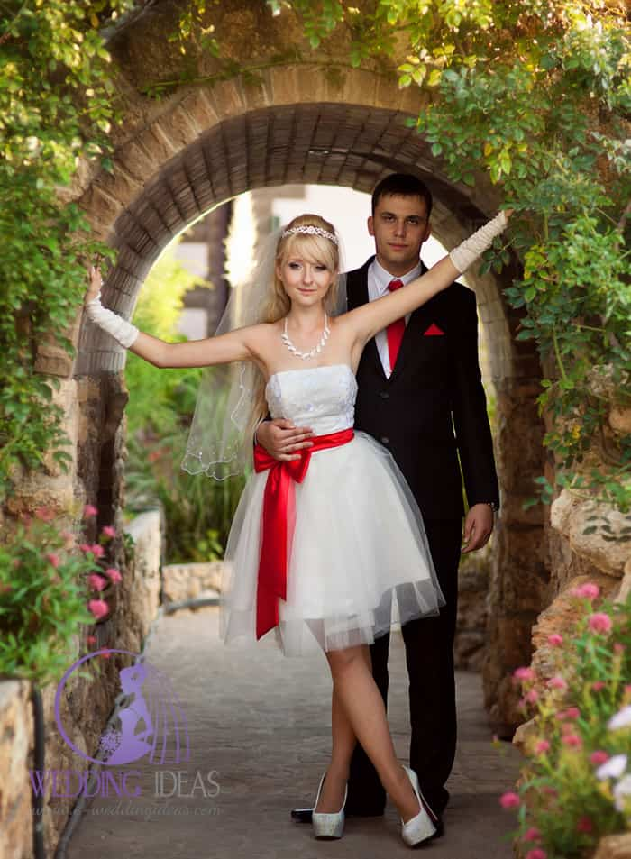 114. Straight necklace with lace design on the bodice, short tulle skirt and red satin bow in the waist. Groom match to Bride, he have red tie and handkerchief.