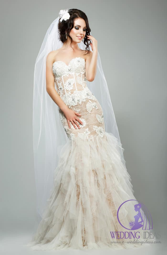 Fit-and-flare wedding dress with lace appliqués, sweetheart neckline, and sheer illusion bodice with tulle skirt.