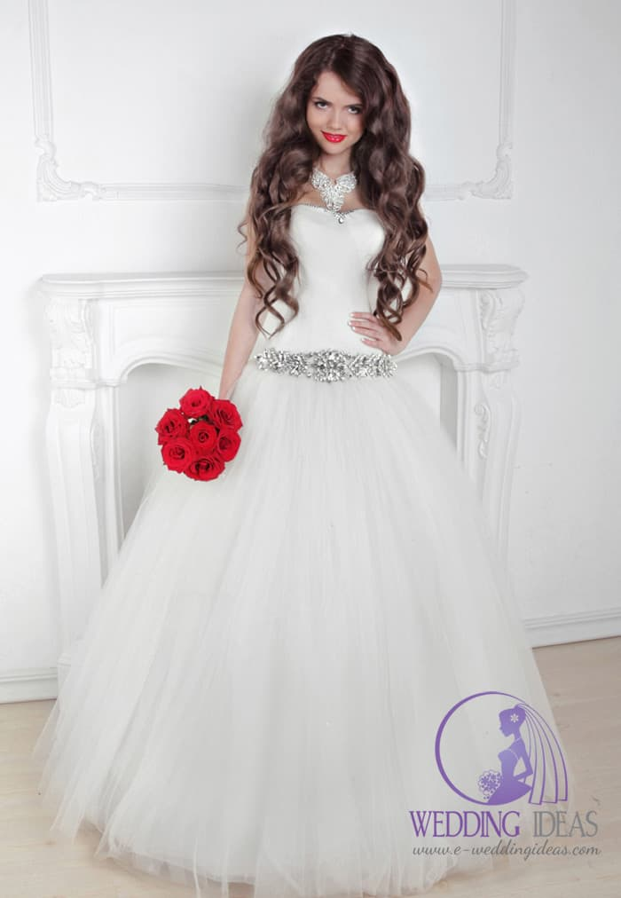 122. Ball gown, satin bodice with crystals on the top. Big silver crystal belt in the waist and long tulle skirt. Red lips similar to red rose bouquet. Long curly brown hair.