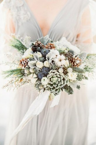 A bouquet made of green leaves and white and brown flowers