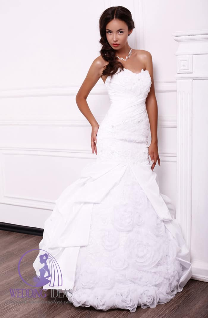 Bride dress has ball gown with sweetheart necklace. Layered skirt with tulle roses in the middle.