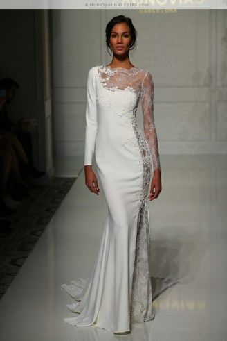 A white long-sleeved wedding dress with an asymmetric-shaped bust.