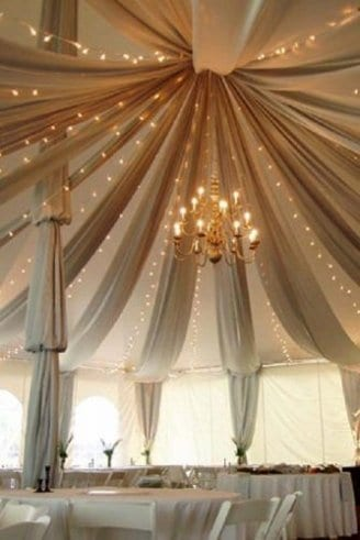 A romantic grey wedding tent with matching seats, white table cloths and flowers