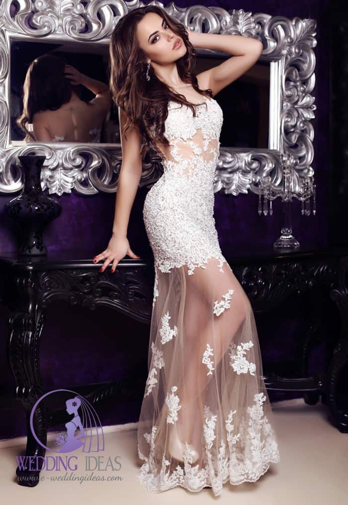 132. See through lace wedding dress, with illusion necklace. White high heels hide in the skirt. Long dark brown curly hair. Mirror in silver frame in the background.