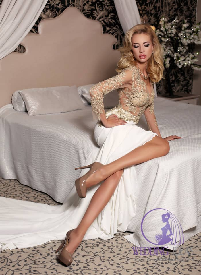 134. Gold whole in crystal see through bodice with long sleeve. Long white smooth skirt. Nude high heels on the feet. She sits on the bed.
