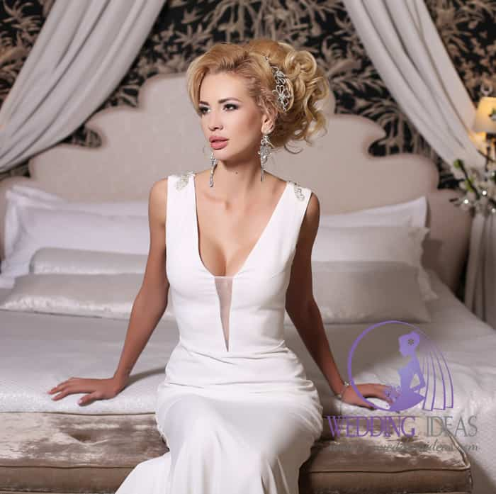135. A-line with V-neck, whole smooth bride dress. Pinned up blonde hair with crystal hair band in. Big and long crystal earrings. Bedroom in the background.