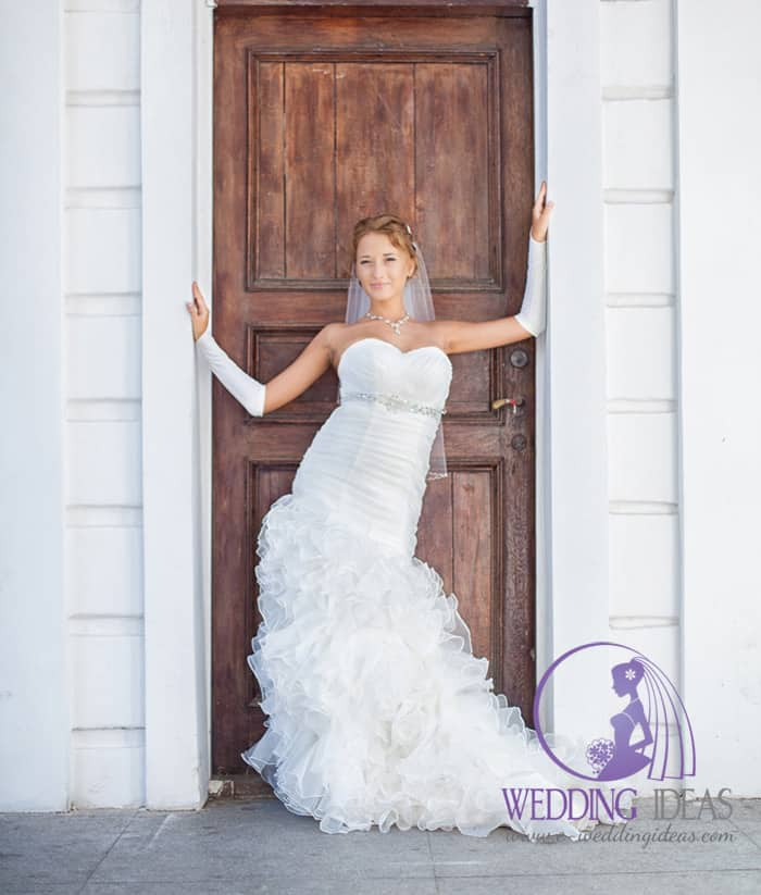 Satin fit-and-flare gown, with tulle skirt with short train and crystal belt on bodice under sweetheart necklace.
