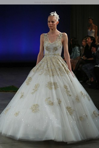 A white gown with spaghetti straps. It has grey patches all over it and has a wide base.