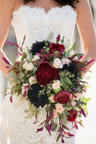 round red and black flowers and small white flowers combined with green leaves and green flower buds
