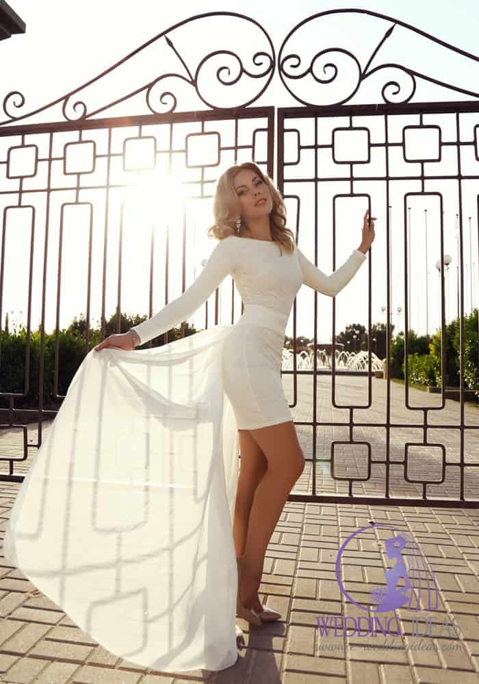 Short bride dress with long sleeve, long train going from belt on her waist.