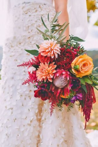 A lovely bouquet comprised of round yellow and red flowers and green leaves