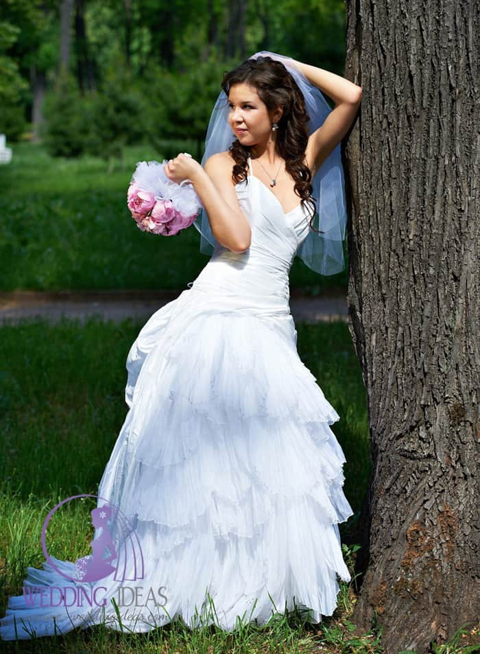 Bride dress has satin spaghetti strap with V-neck and tulle skirt with train