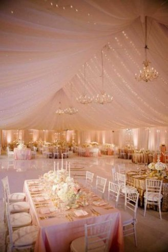 A romantic brown wedding tent with white seats and matching flowers