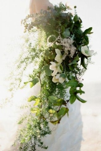 A beautiful bouquet consisting of white flowers, white flower buds, and strings of green leaves