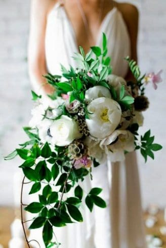 A beautiful wedding bouquet made of large white flowers mixed with green leafy flowers