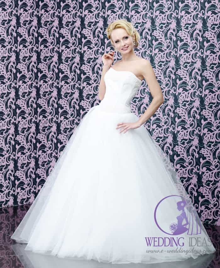 160. Wedding dress has ball style with straight necklace, shiny pearl design on the bust. Long tulle skirt. Pinned up blonde hair, dark eye makeup and shiny nude lips.