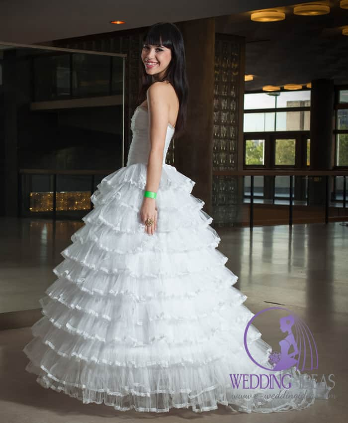 161. Ball wedding gown with straight necklace. Layered lace skirt with design on the end of every layer. Short train going from skirt. Black straight hair with forelock. Dark eye makeup and shiny pink lips.