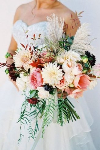 A pretty bouquet consisting of white, pink and green flowers and green flower buds and leaves held by the bride