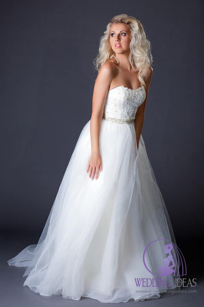 162. Ball gown with straight necklace, violet belt in the waist with crystal in the middle of bow. Long tulle layered skirt. Curly blond hair and delicate makeup.