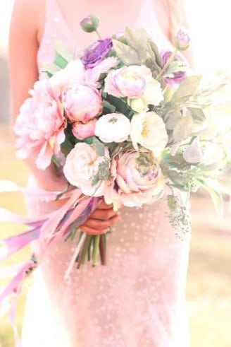 A beautiful wedding bouquet made of round white and pink flowers mixed with leafy green and purple flowers