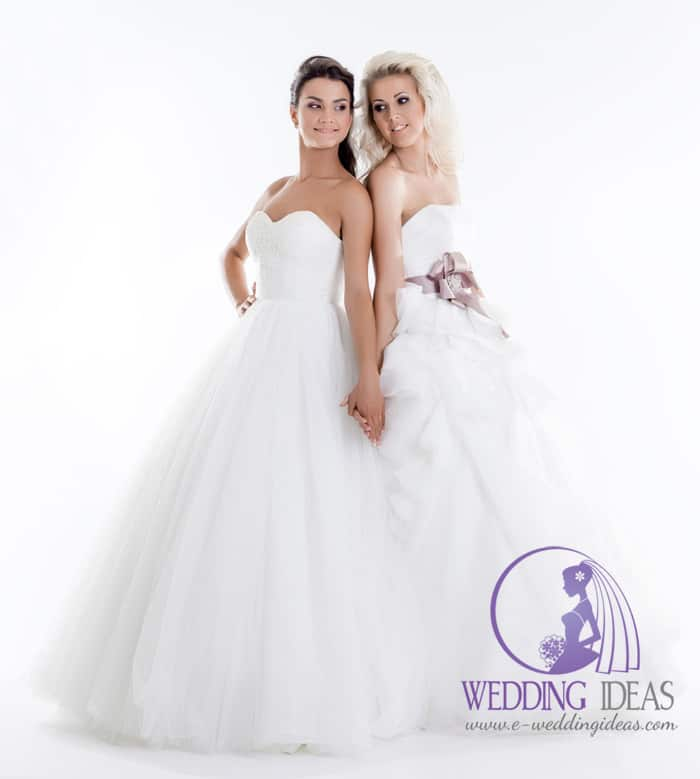 164. Two beautiful Brides. Women from left side have ball gown with sweetheart necklace, and long tulle skirt. Long brown hair and delicate makeup. Women on the right have curly blond hair, ball gown with straight necklace. Violet belt in the waist with crystal in the middle of bow, and long tulle layered skirt.