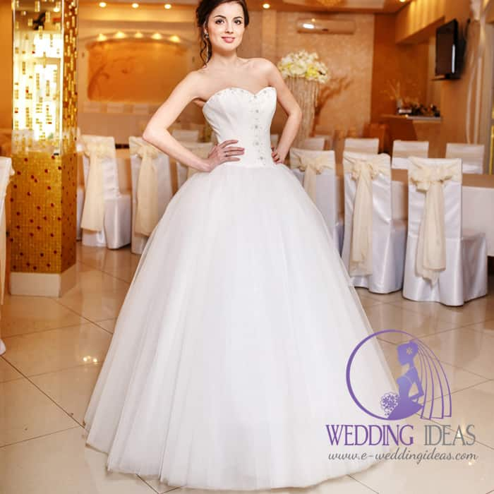 169. This is a wedding dress has ball  style with sweetheart necklace. Crystal design on the bodice and long tulle skirt. Pinned up brown hair and delicate makeup. Wedding hall in the background.