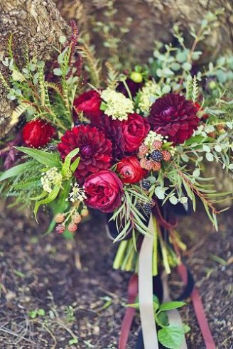 A beautiful bouquet consisting of round red and green leafy flowers tied with a green ribbon