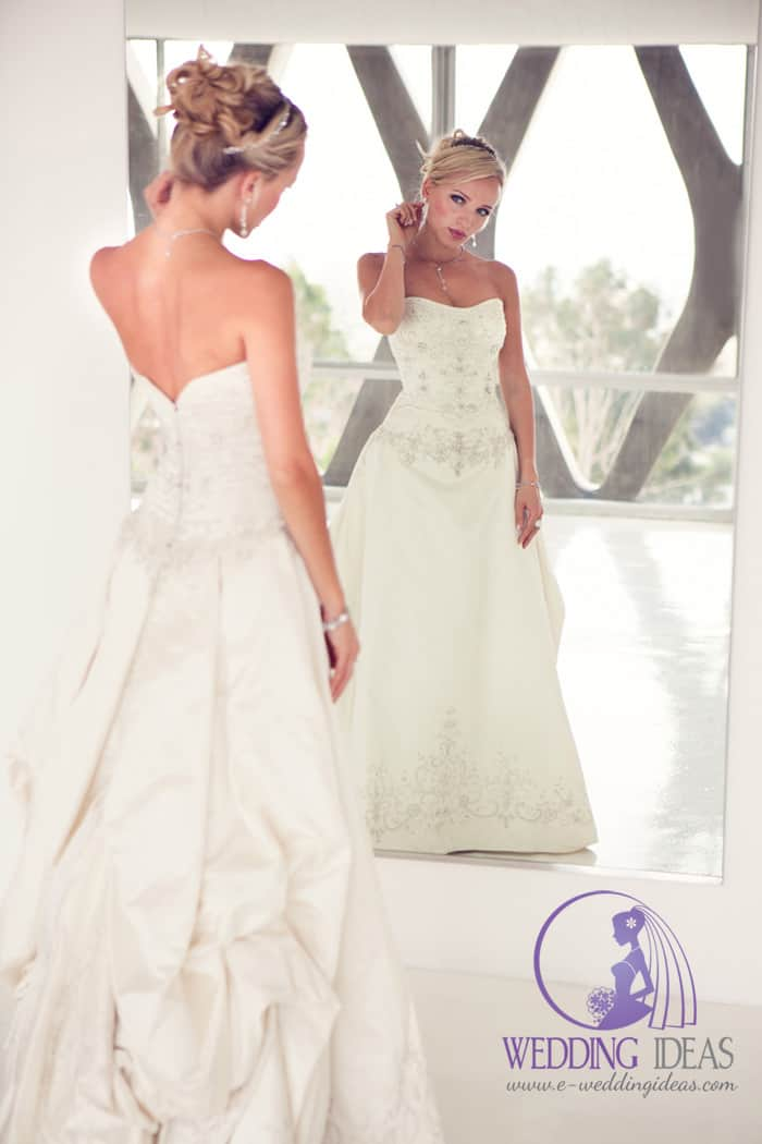 A-line bridal dress with lace and crystals in the bodice and bottom of the skirt. Delicate and elegant crystal diadem, necklace, earrings, and bracelet. Hide zip on the back.