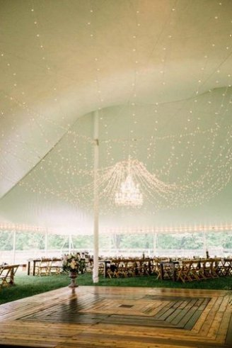 A beautiful white wedding tent with brown seats and white and pink flowers hanging on its roof