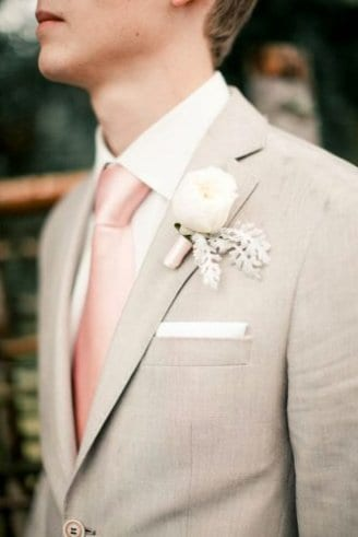 A bridegroom in a black blazer, white shirt, pink tie, white pocket square and a white boutonniere