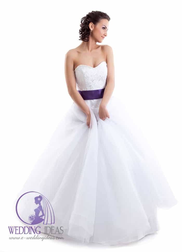 173. Ball gown with sweetheart necklace. Crystal design on the bodice and navy satin belt in the waist, long tulle skirt. Pinned up curly brown hair. Dark eye makeup up and shiny pink lips.