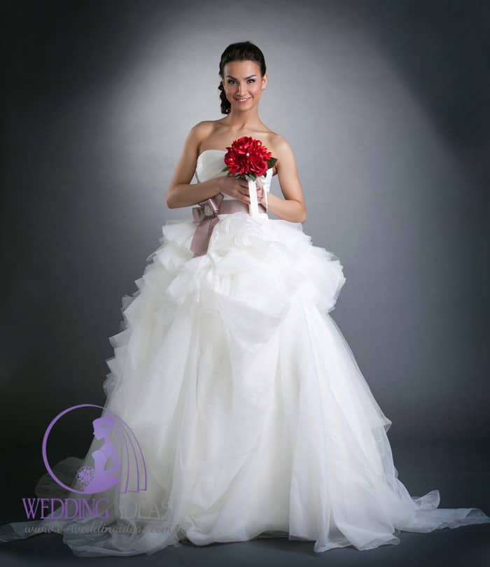 174. Ball gown with straight necklace and layered tulle skirt. Violet belt in the waist with crystals inside the bow. Red bouquet hold on the bust in both hands.