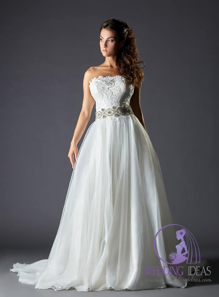 176. Ball gown with straight necklace. Lace bodice with crystal belt on the waist. Long tulle skirt with train. Brown curly hair and delicate makeup.