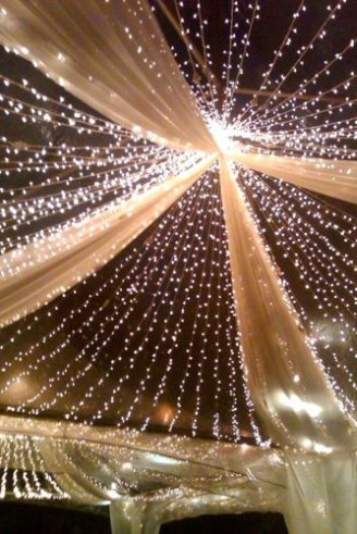 A romantic white wedding tent with white seats and red and pink flowers hanging on the roof