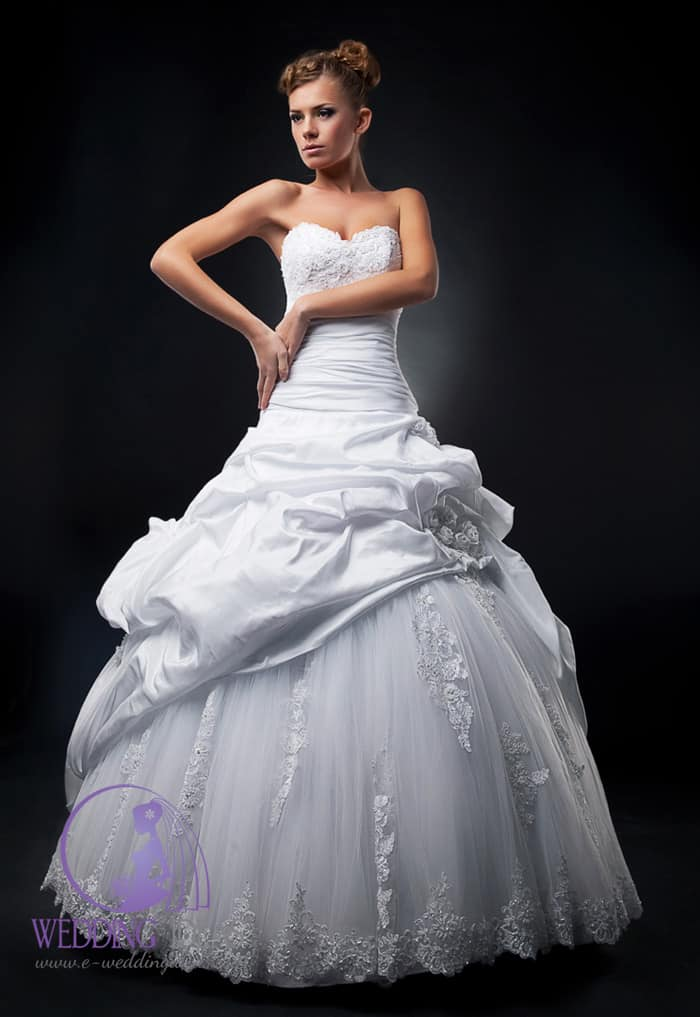 183. A-line gown with sweetheart necklace on spaghetti straps. Lace design on the bust and wide satin belt in the waist. Smooth long skirt with lace design on the end. Vintage look pinned up blonde hair.