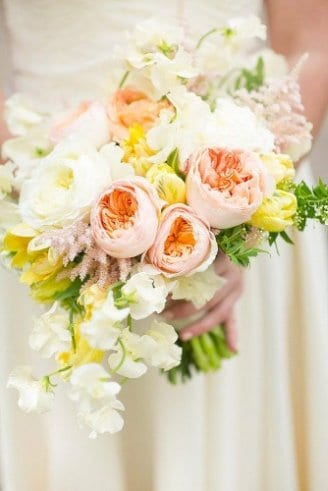 A lovely wedding bouquet made of round pink and white flowers together with green leaves